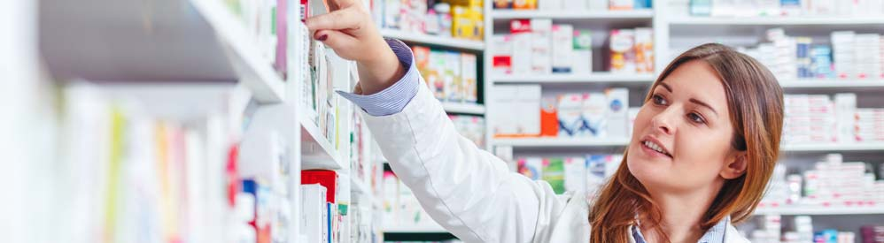 pharmacist pointing at meds on shelf