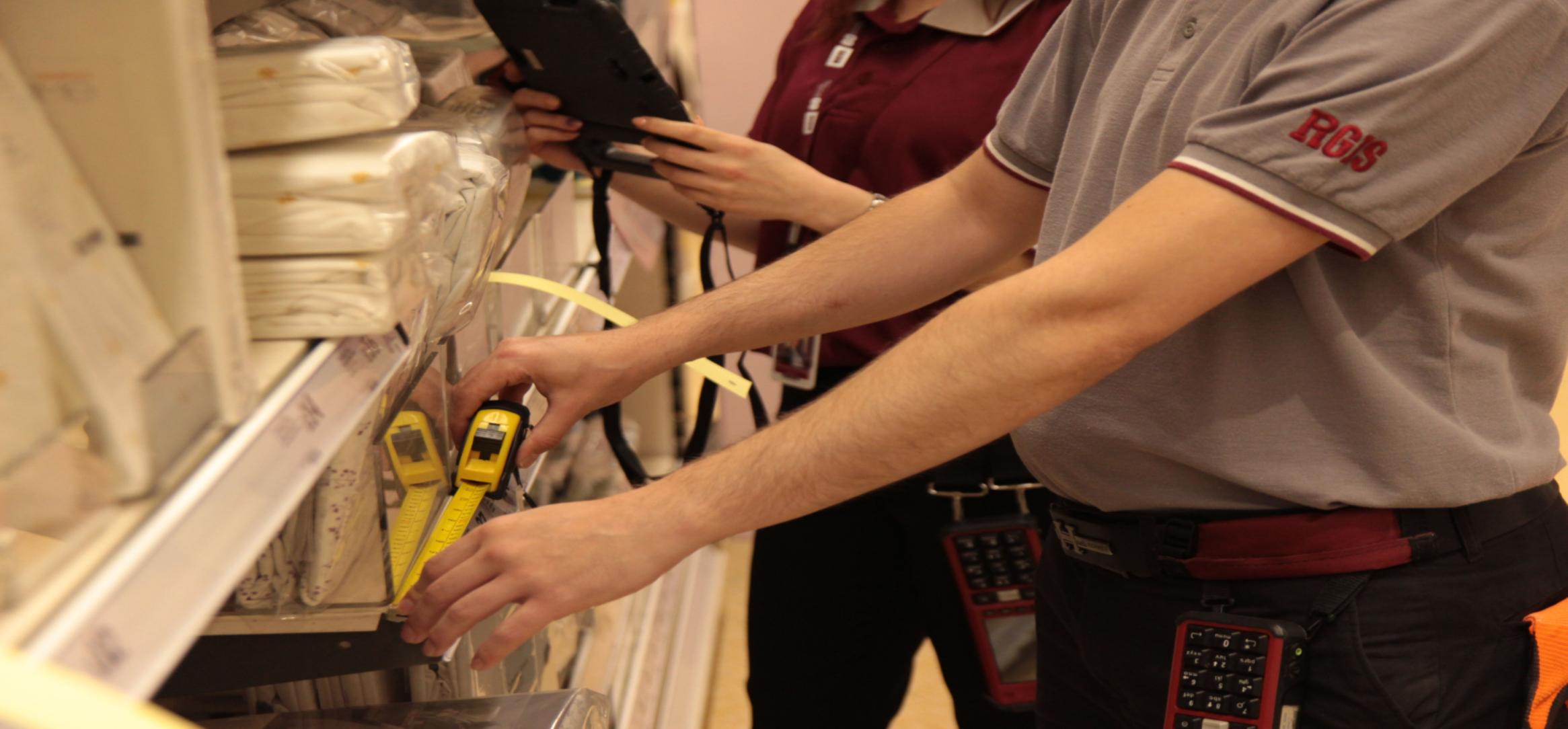 2 RGIS auditors measuring a shelf as part of a fixture audit