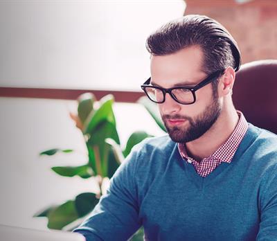 Man sat at laptop checking stock availability