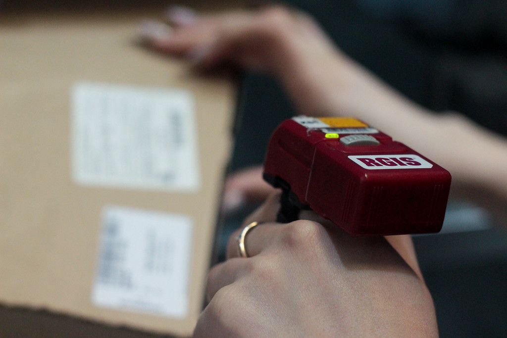 An RGIS finger laser scanning a parcel delivery in a warehouse