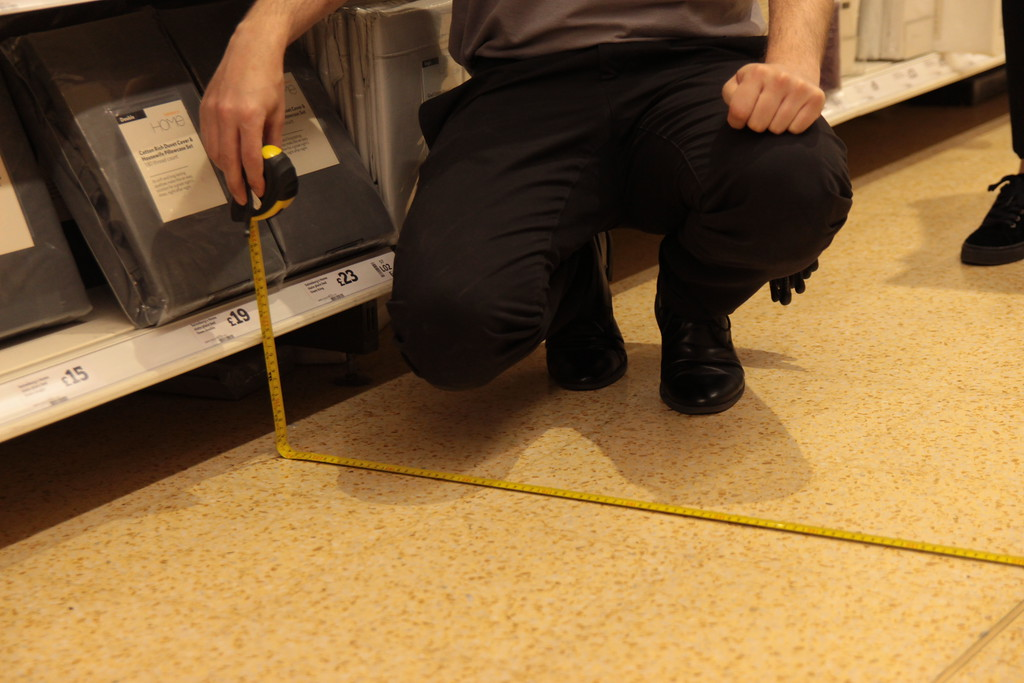 RGIS auditor using a tape to measure the store