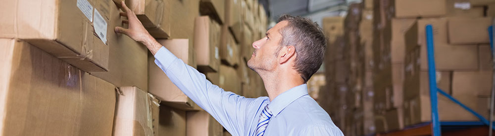 Man checking boxes holding warehouse stock