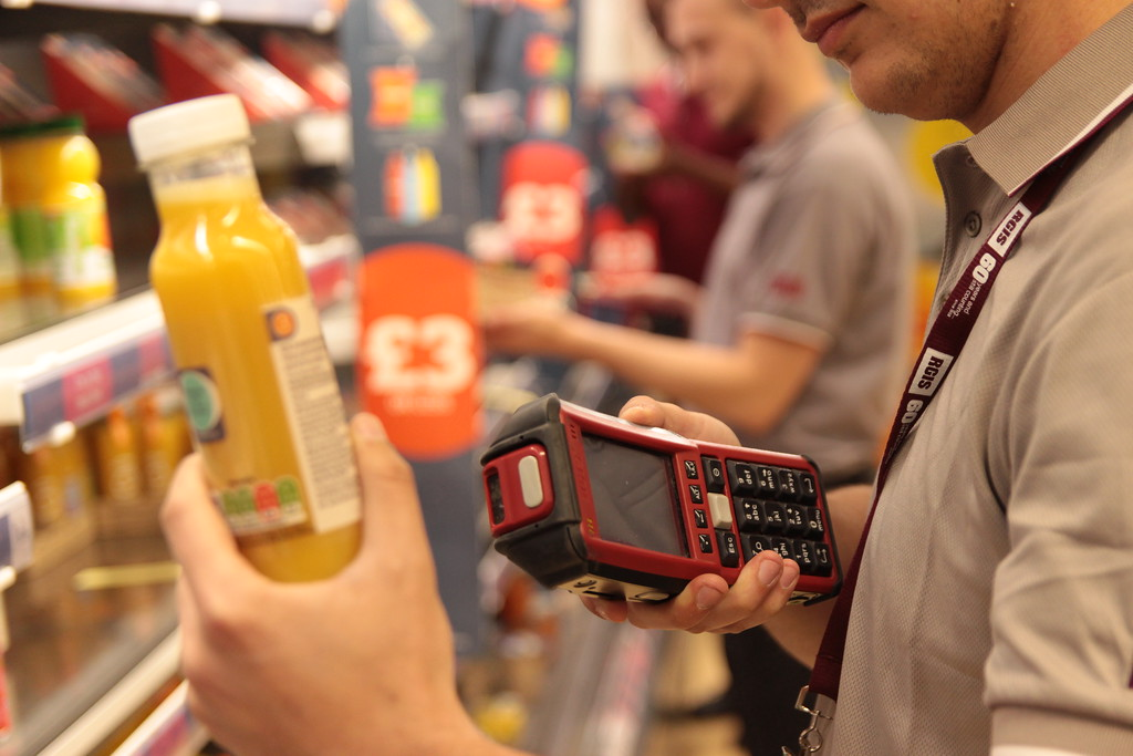 RGIS auditor scanning a bottle of orange juice as part of a stocktake