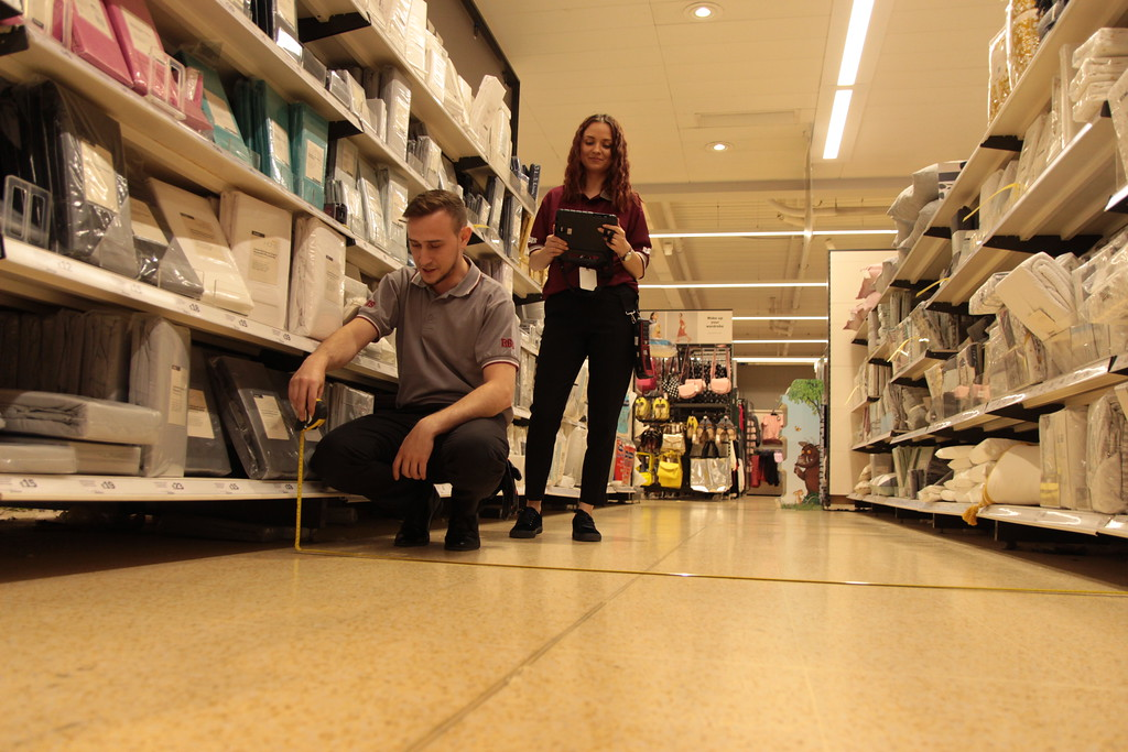2 RGIS auditors measring the distance of an aisle in a retail store for space planning